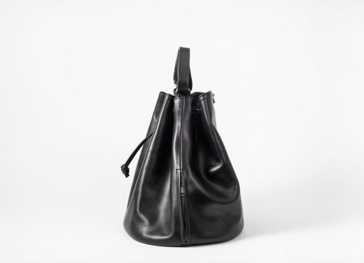 Side view on a black vegetable tanned leather Bucket Bag with a short handle and a string passing the eyelets